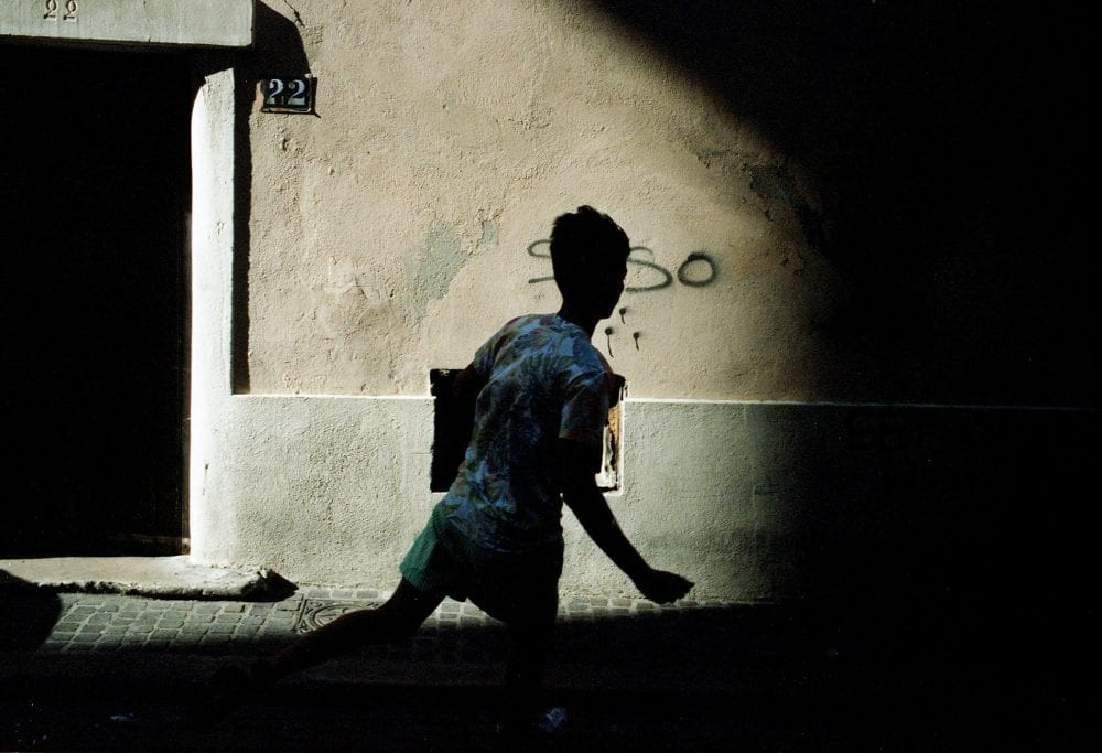 street photography, urban life, composing colorful interactions, with light and shadow, by Chris Garvi in Marseille