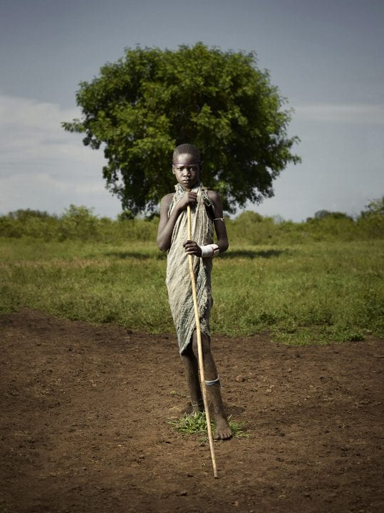 portrait of a man from a tribe in the nature, omo valley by Ken Hermann
