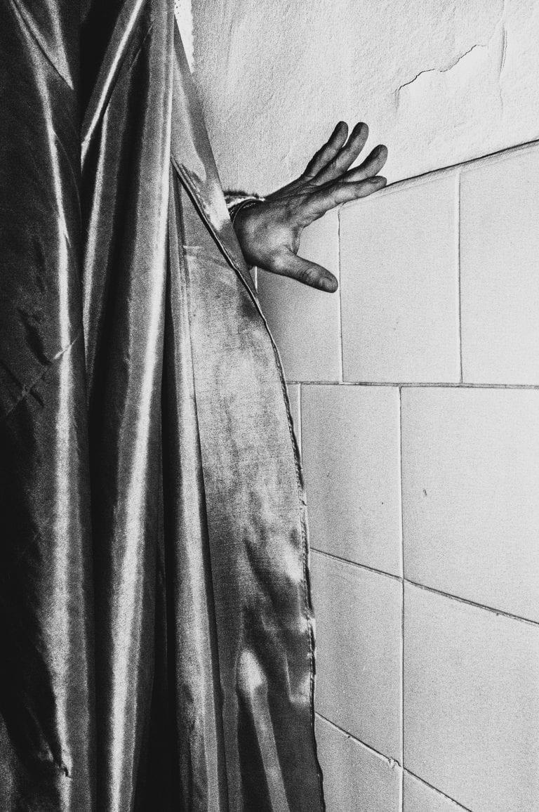 hand behind shower curtain black and white photography with high contrast and flash by francesco merlini