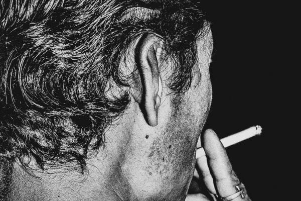 man smoking black and white photography with high contrast and flash by francesco merlini