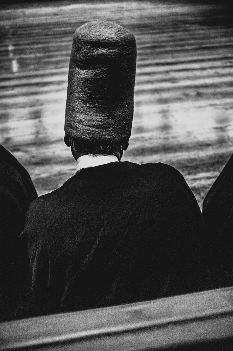 hombre vestido con sombrero fotografía en blanco y negro con alto contraste y flash por francesco merlini