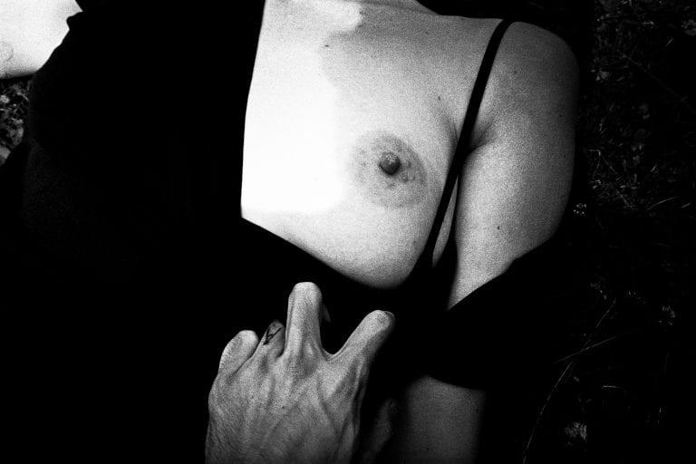 Fotografía en blanco y negro de mama de mujer, profundidad de campo baja, alto contraste, por Francesco Merlini