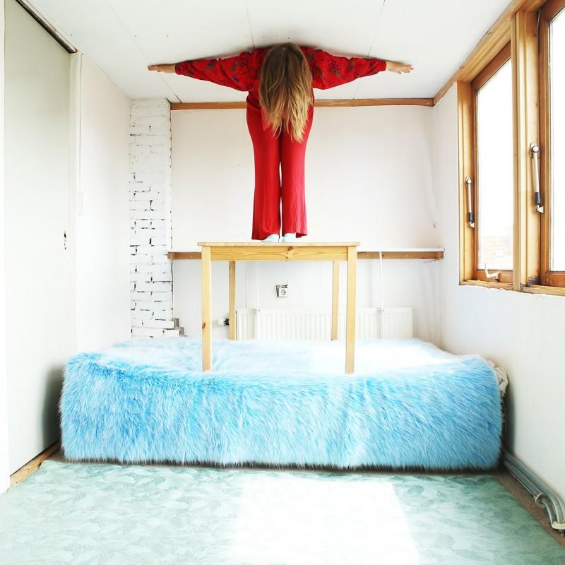 woman on blue bed color photography by inge van heerde