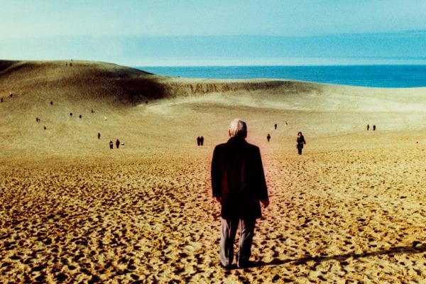 man standing on the beach from the sunlanders series, color darkroom prints handmade by Sean Lotman