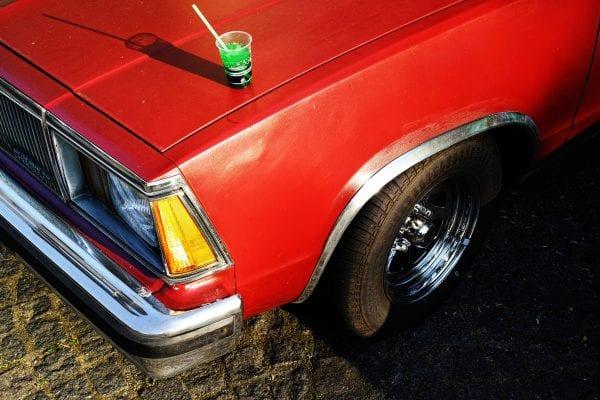Fotografía callejera de coche rojo, colorida, por Manuel Armenis