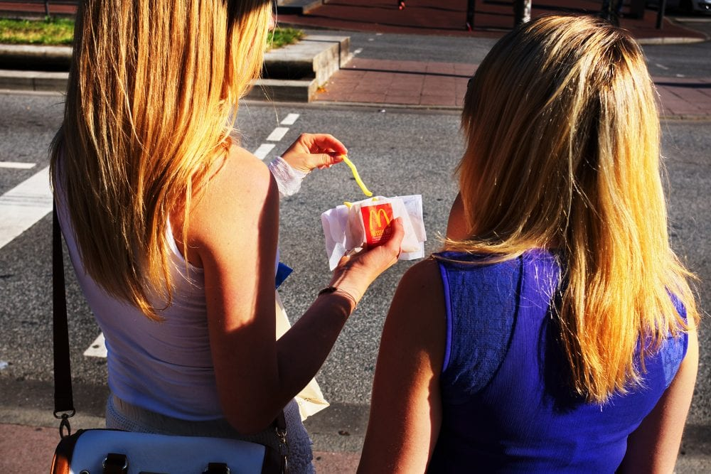 two girls eating mcdonalds fries street photography, colorful, by Manuel Armenis