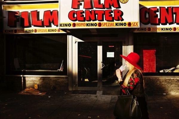 Mujer delante de una tienda de fotografía callejera, colorida, por Manuel Armenis