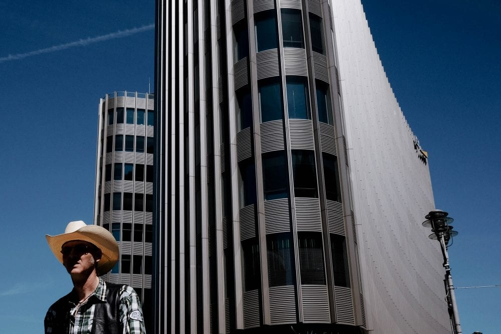 man wearing a hat standing in front of a building street photography of a person, by efi logginou
