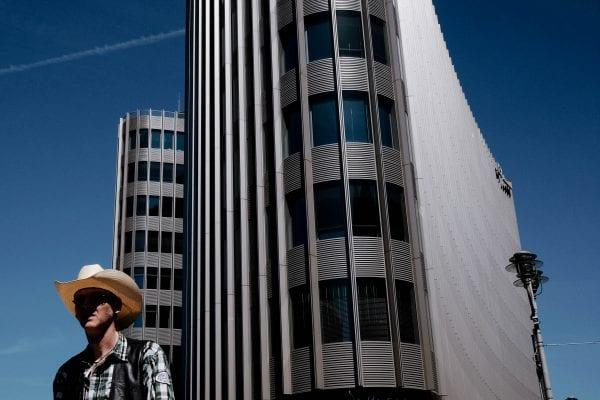 hombre con sombrero parado frente a un edificio fotografía callejera de una persona, por efi logginou