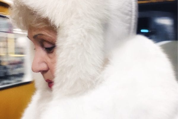 woman wearing white fur street photography of a person, by efi logginou