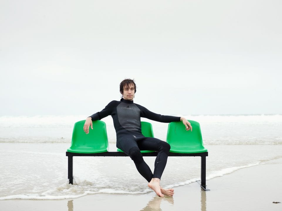 swimmer suit, man sitting on a green bench, color portrait photography by dylan collard