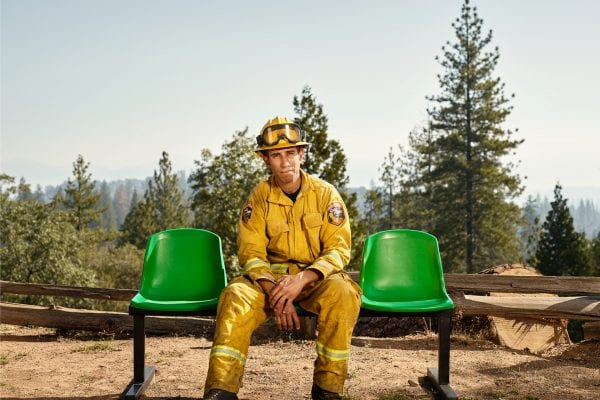 fireman sitting on a green bench, color portrait photography by dylan collard
