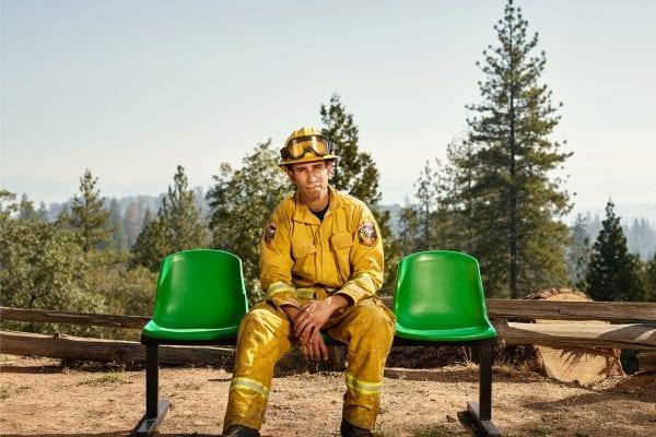 pompier assis sur un banc vert, photographie de portrait couleur par dylan collard