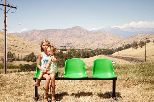 woman and kid sitting on a green bench, color portrait photography by dylan collard