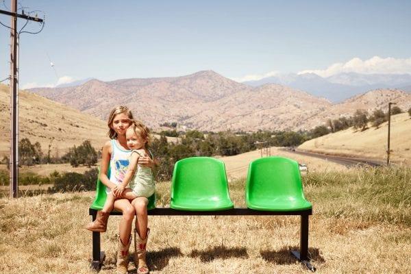 Femme et enfant assis sur un banc vert, photographie de portrait couleur par dylan collard