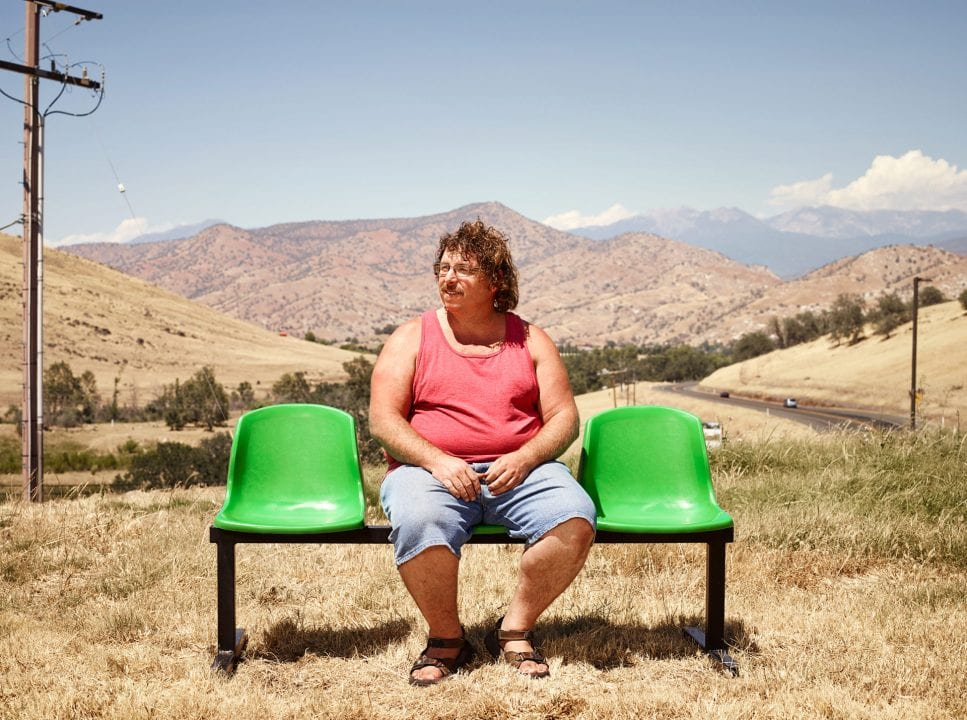 man sitting on a green bench, color portrait photography by dylan collard