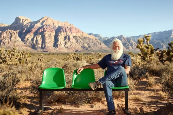 bearded man sitting on a green bench, color portrait photography by dylan collard