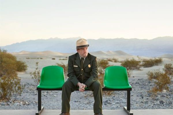 Homme portant un chapeau et assis sur un banc vert, photographie de portrait couleur par dylan collard