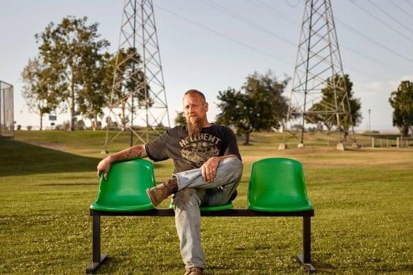 homme assis sur un banc vert, photographie de portrait couleur par dylan collard
