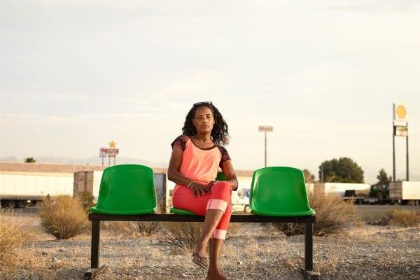 Femme assise sur un banc vert, photographie de portrait couleur par dylan collard