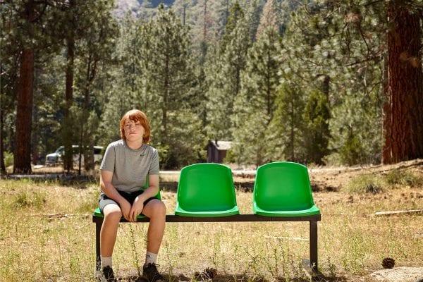 Jeune homme assis sur un banc vert, photographie de portrait couleur par dylan collard