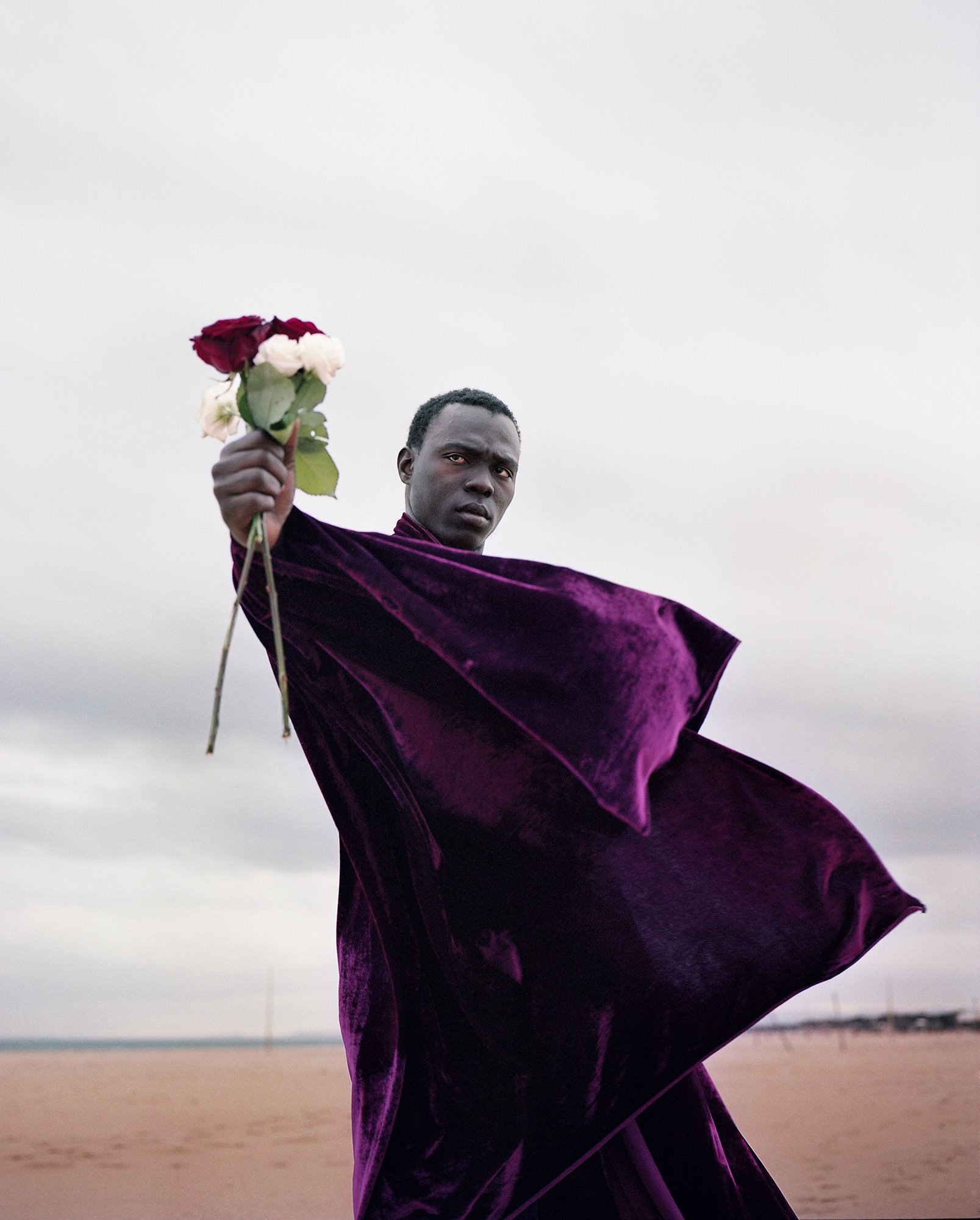 man on a beach holding a flower, color photography of the migration into Europe in 2015 2016