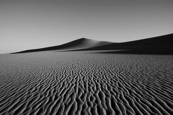 Fotografía de paisaje en blanco y negro de alto contraste de una duna de arena en el desierto