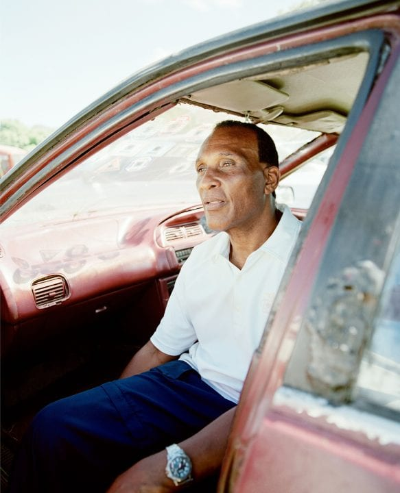 man sitting in car color portrait photography in the Caribbean island of Nevis, by Catherine Hyland
