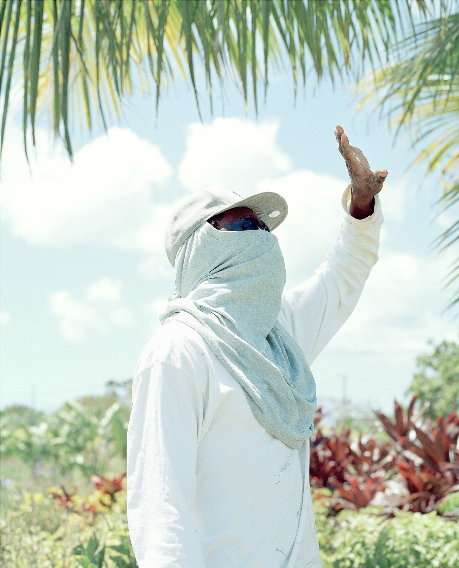 man gardening with white sheet color portrait photography in the Caribbean island of Nevis, by Catherine Hyland