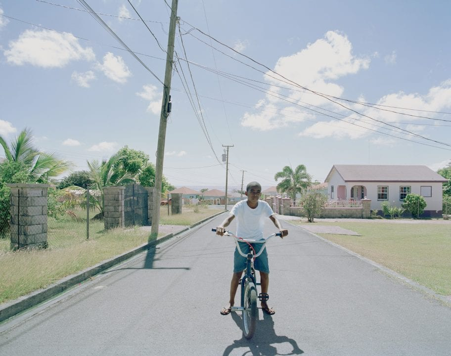 kid on a bike color portrait photography in the Caribbean island of Nevis, by Catherine Hyland