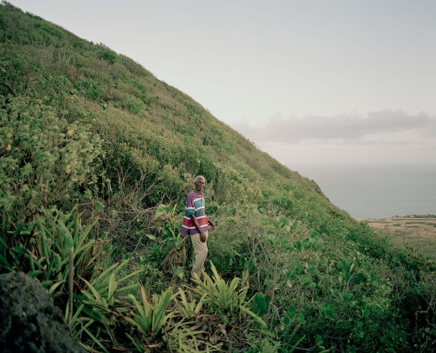 man standing on a mountain color portrait photography in the Caribbean island of Nevis, by Catherine Hyland