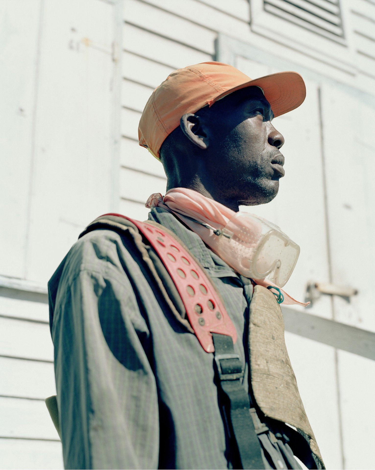 man wearing orange hat color portrait photography in the Caribbean island of Nevis, by Catherine Hyland
