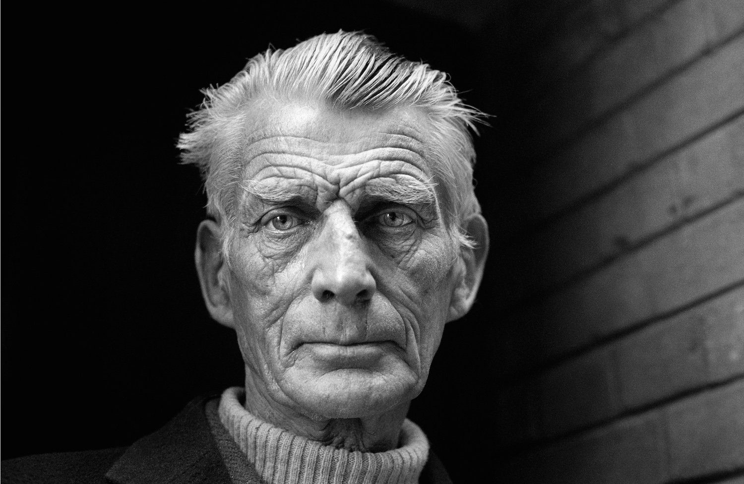 Black and White Photograph of Samuel Beckett leaving the Royal Court Theatre, England 1976 by Jane Bown