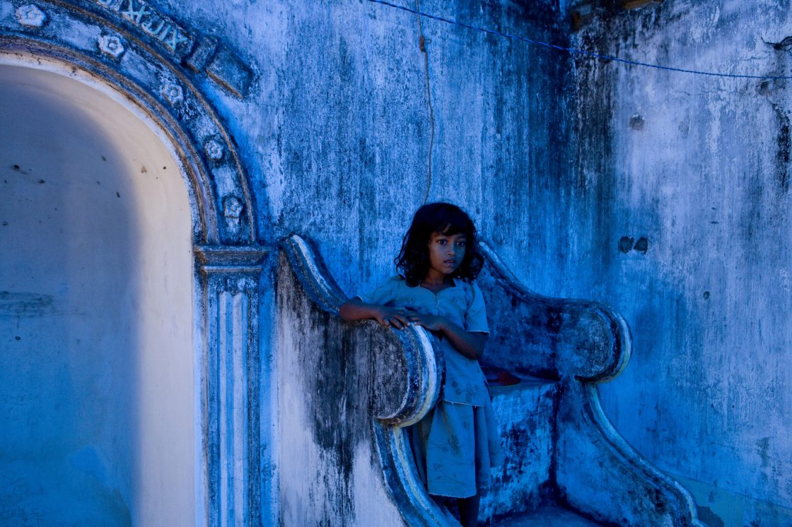 Muslim girl takes up shelter at a destroyed mosque after fleeing a government offensive against the Tamil Tigers in Sri Lanka by Ron Haviv from the VII photo agency
