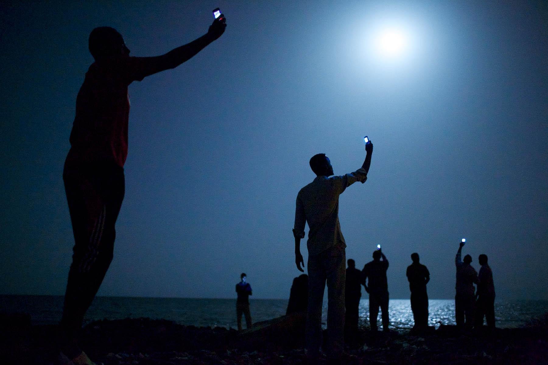 Les migrants africains sur les rives de la ville de Djibouti la nuit lèvent leur téléphone pour tenter d'attraper un signal bon marché John Stanmeyer de l'agence photo VII