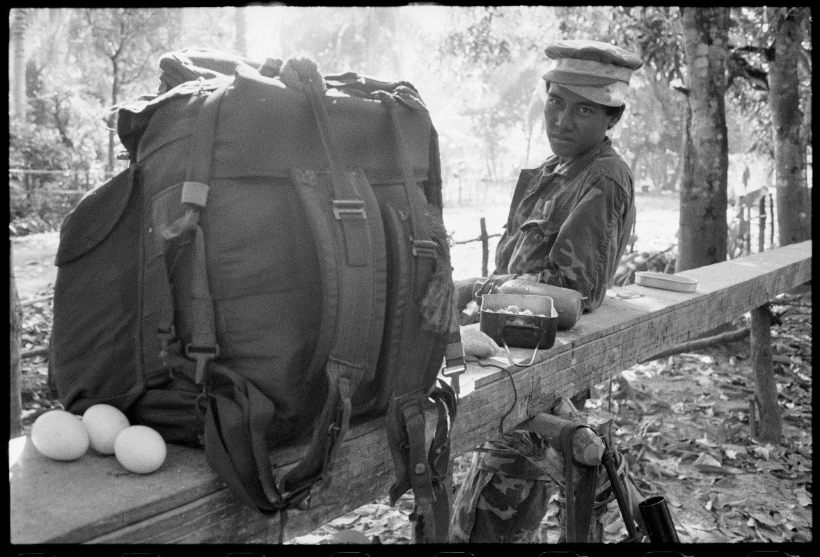 KPNLF soldier with 2 hats and 3 eggs. Cambodia, 1991 by Gary Knight from the VII photo agency