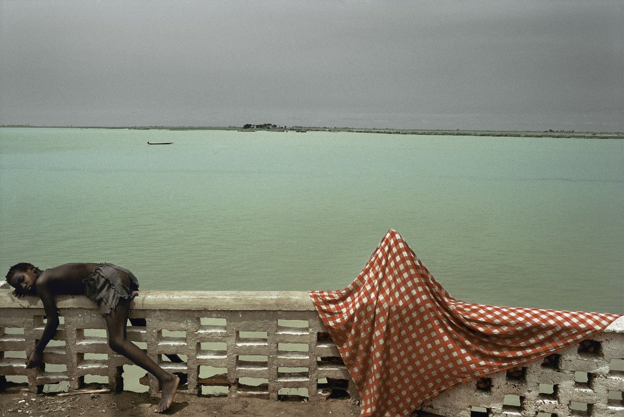 Color photography kid lying next to the water in Mali