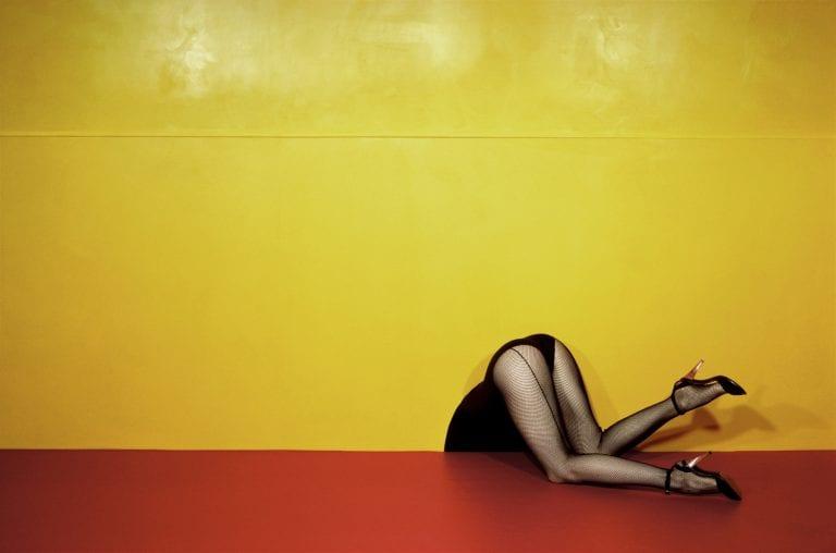 Piernas de mujer fondo amarillo Fotografía en color por Guy Bourdin