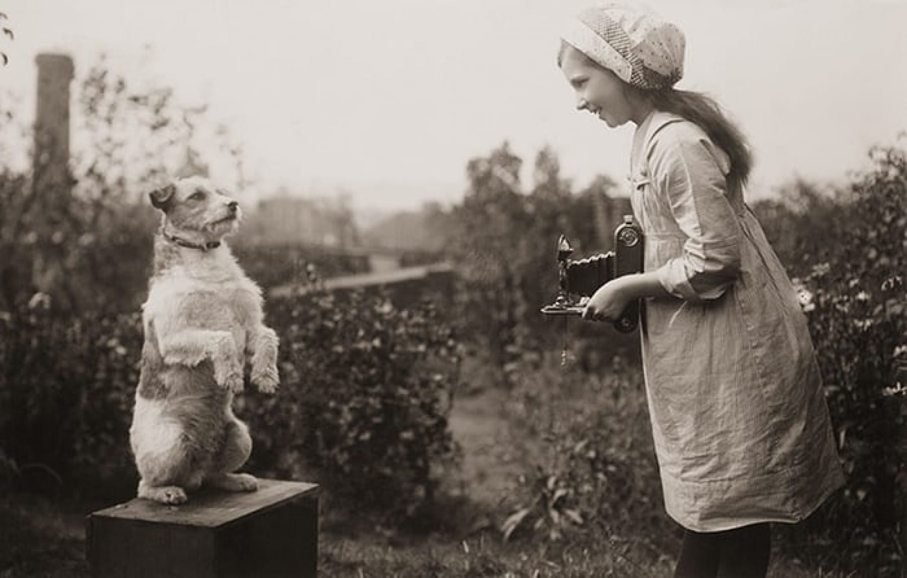 A girl taking a photograph of a dog, 1920's