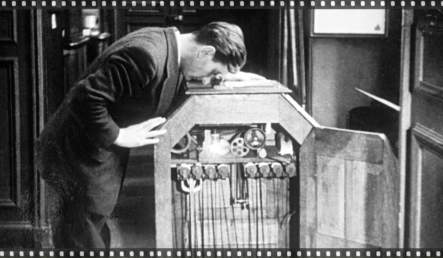 A man watching a moving picture through the Edison kinetoscope, 1889