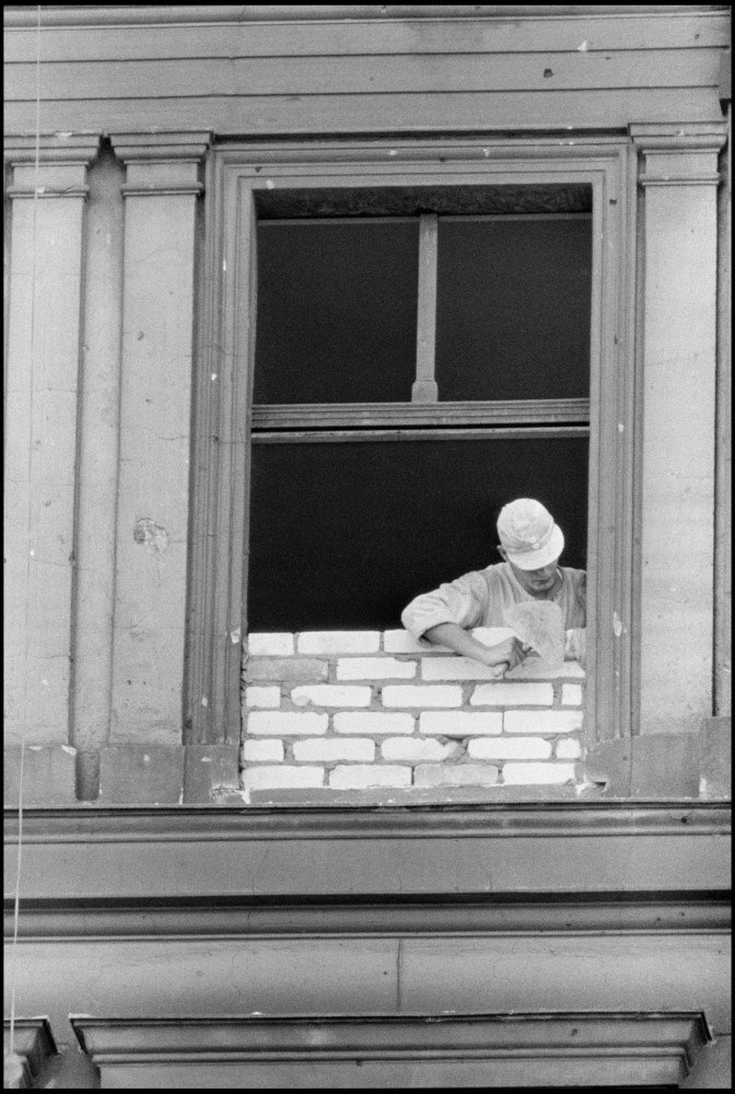 East German Workman Bricking up a window that is due to become part of the wall. West Berlin, Germany, 1961 © Burt Glinn / Magnum Photos