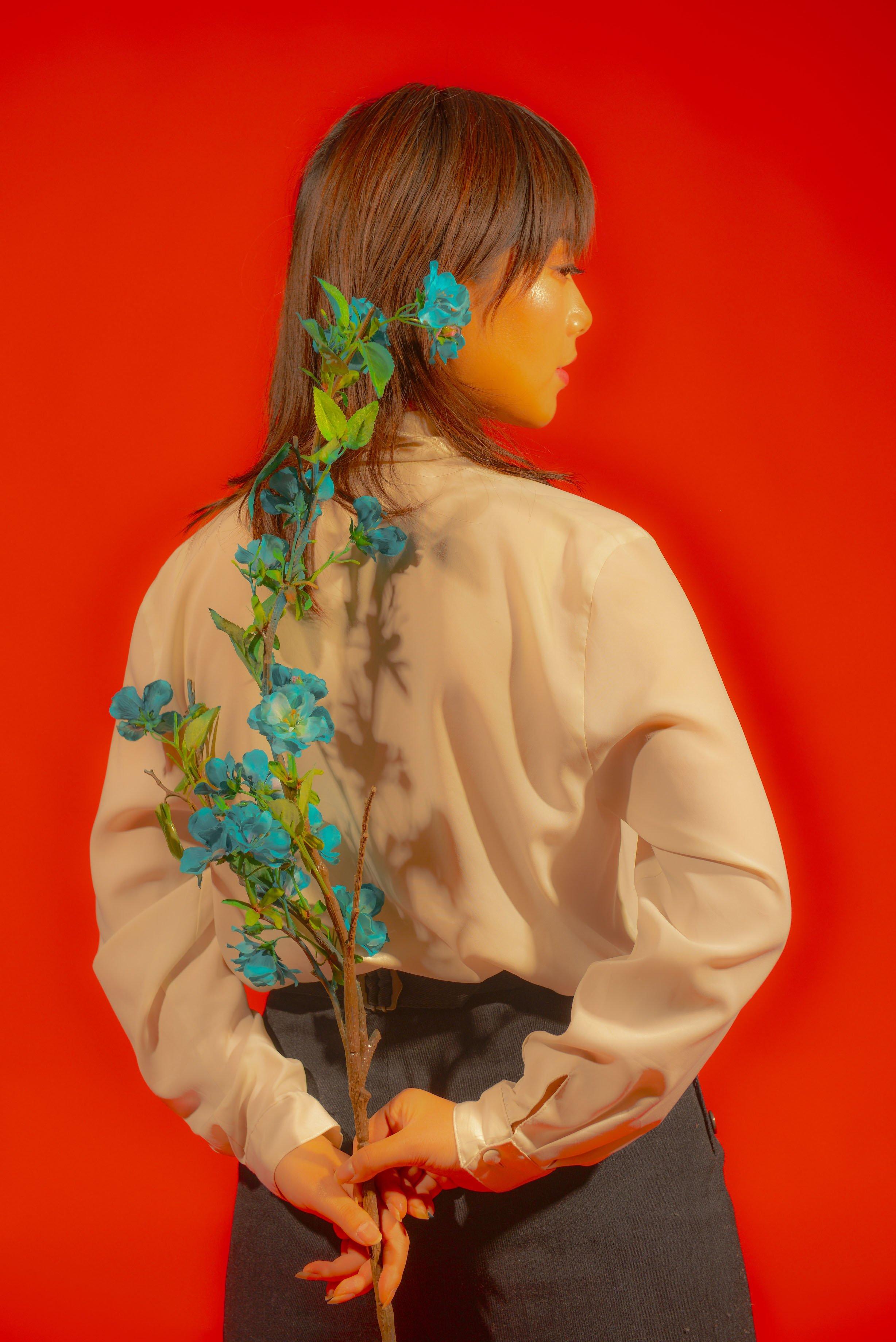 Fotografia a colori, donna con fiore su sfondo rosso