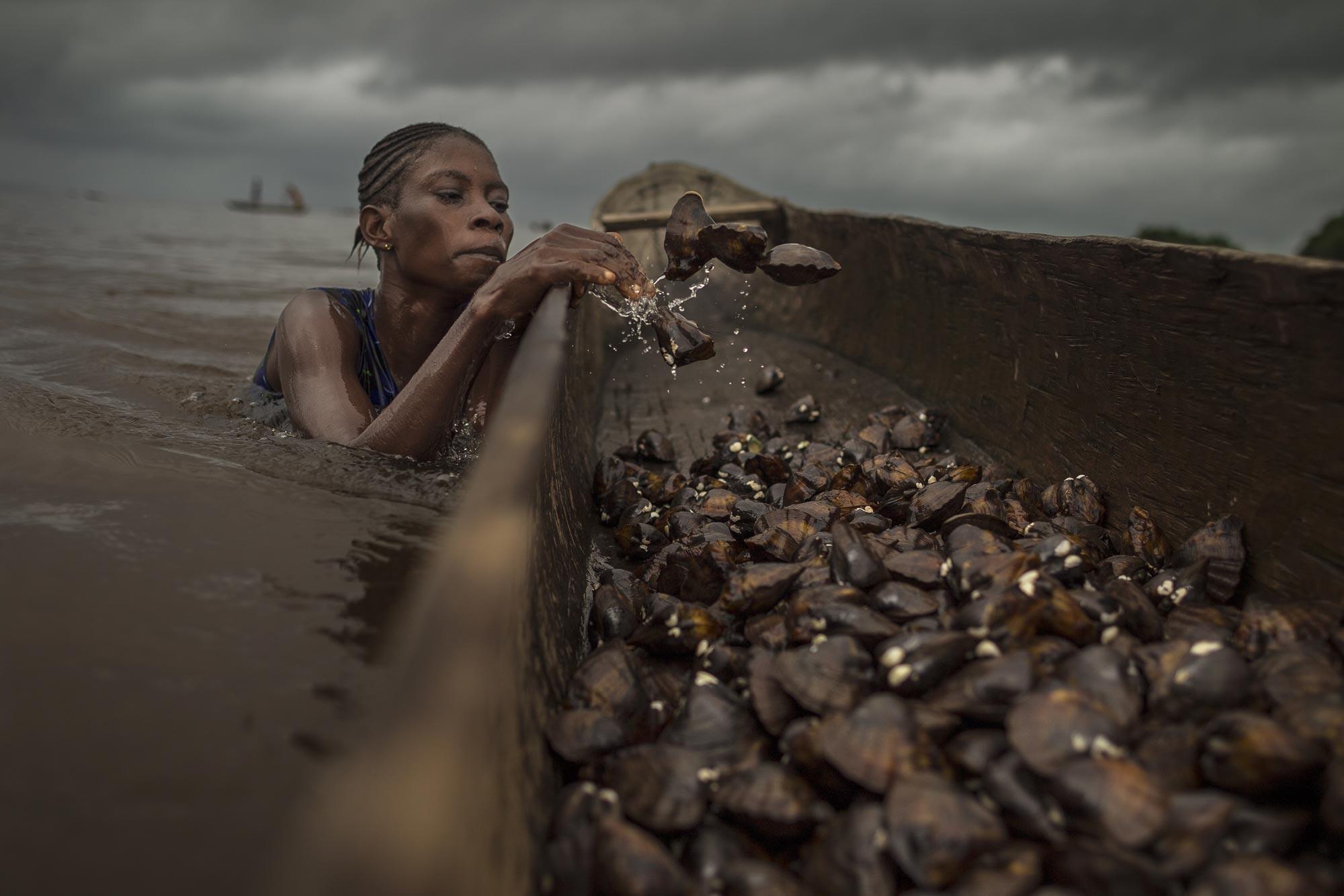 Fotografia documentaria Woman in Water fishing di Kris Pannecoucke