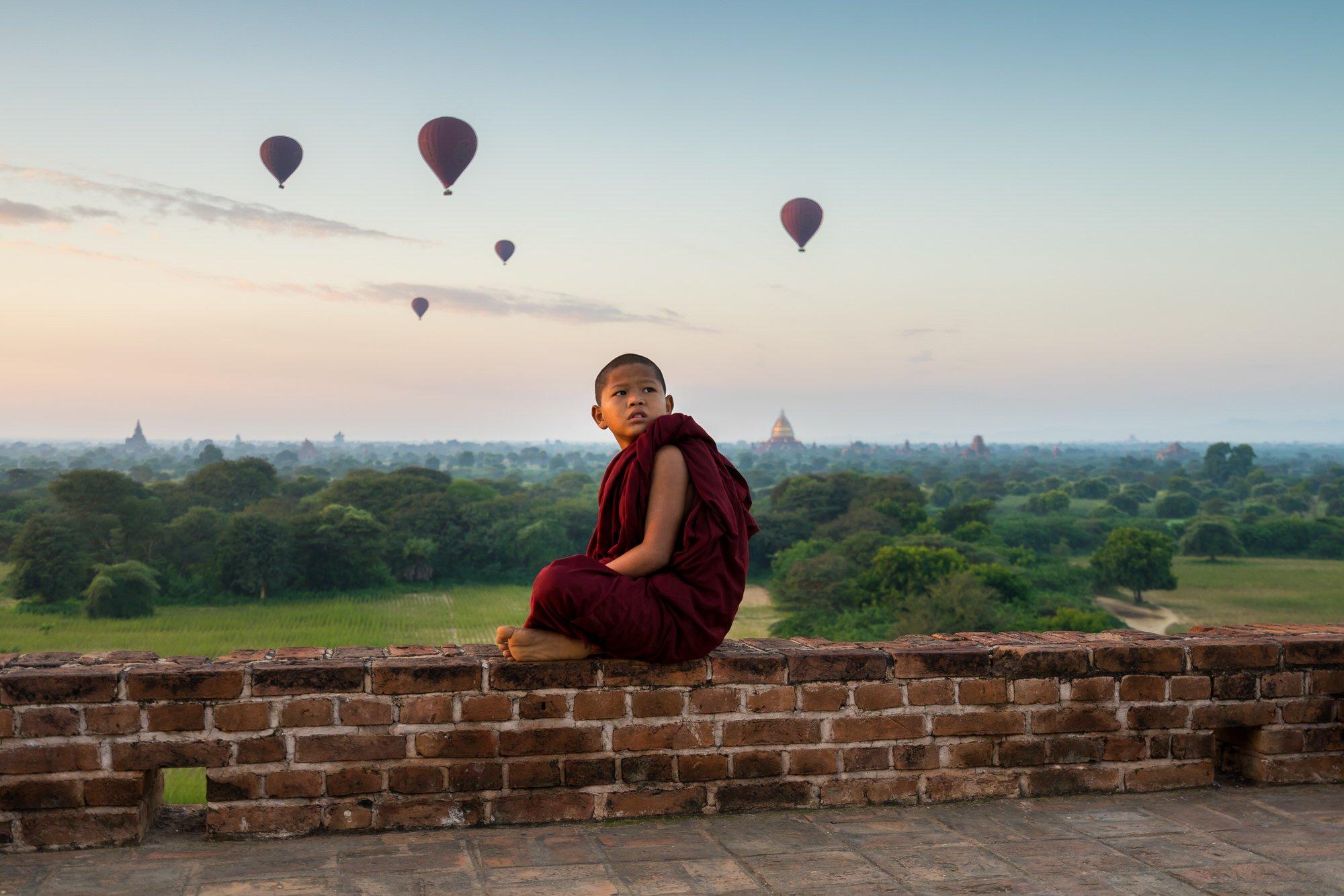 Un jeune moine bouddhiste est à la recherche de montgolfières au lever du soleil