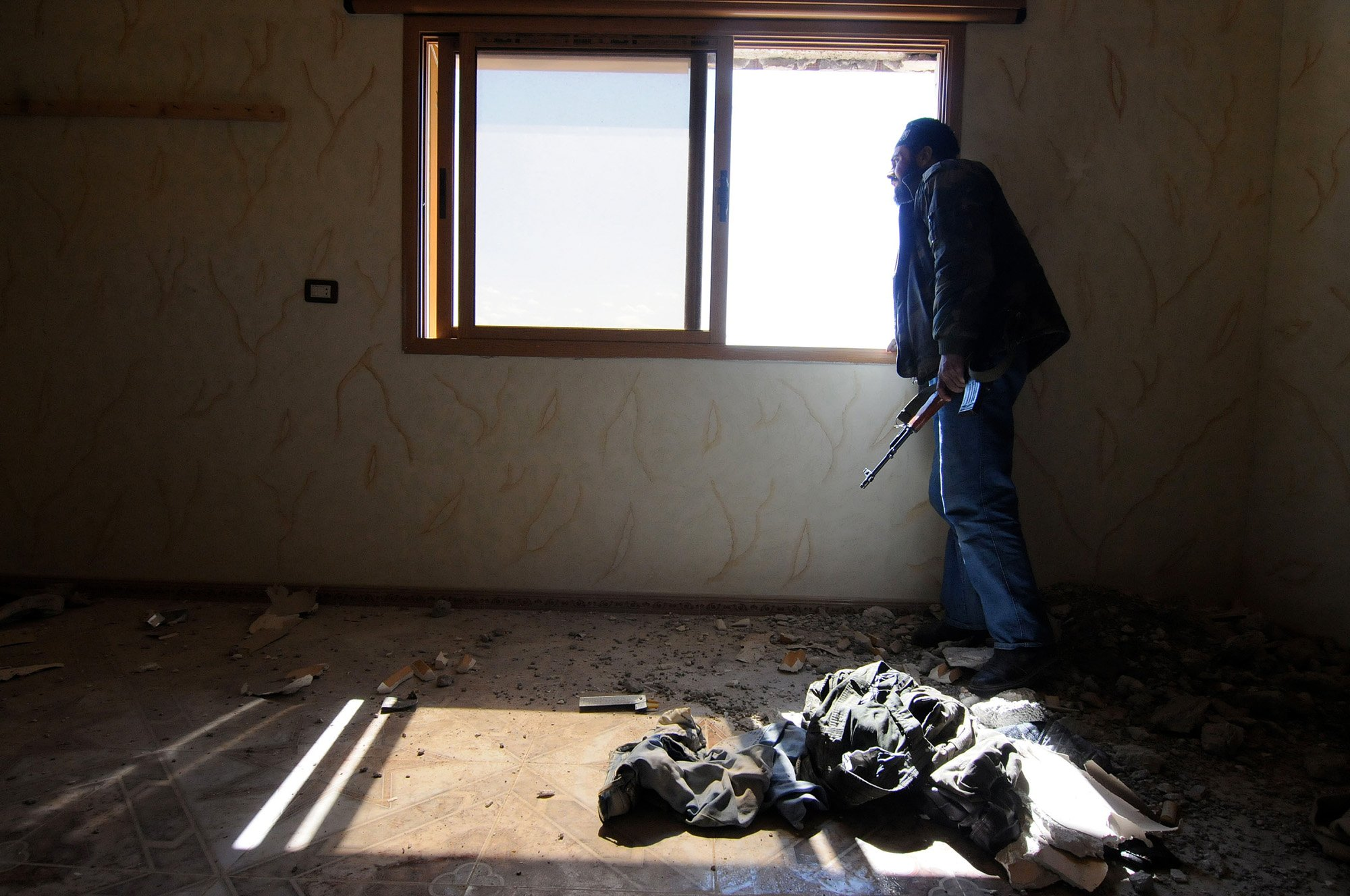 Un combatiente del FSA está al acecho desde el interior de una posición defensiva después de que las fuerzas gubernamentales acabaran de bombardear el área con tanques a 80 km al norte de Damasco - Siria, 25 de abril de 2013, por Jonathan Alpeyrie