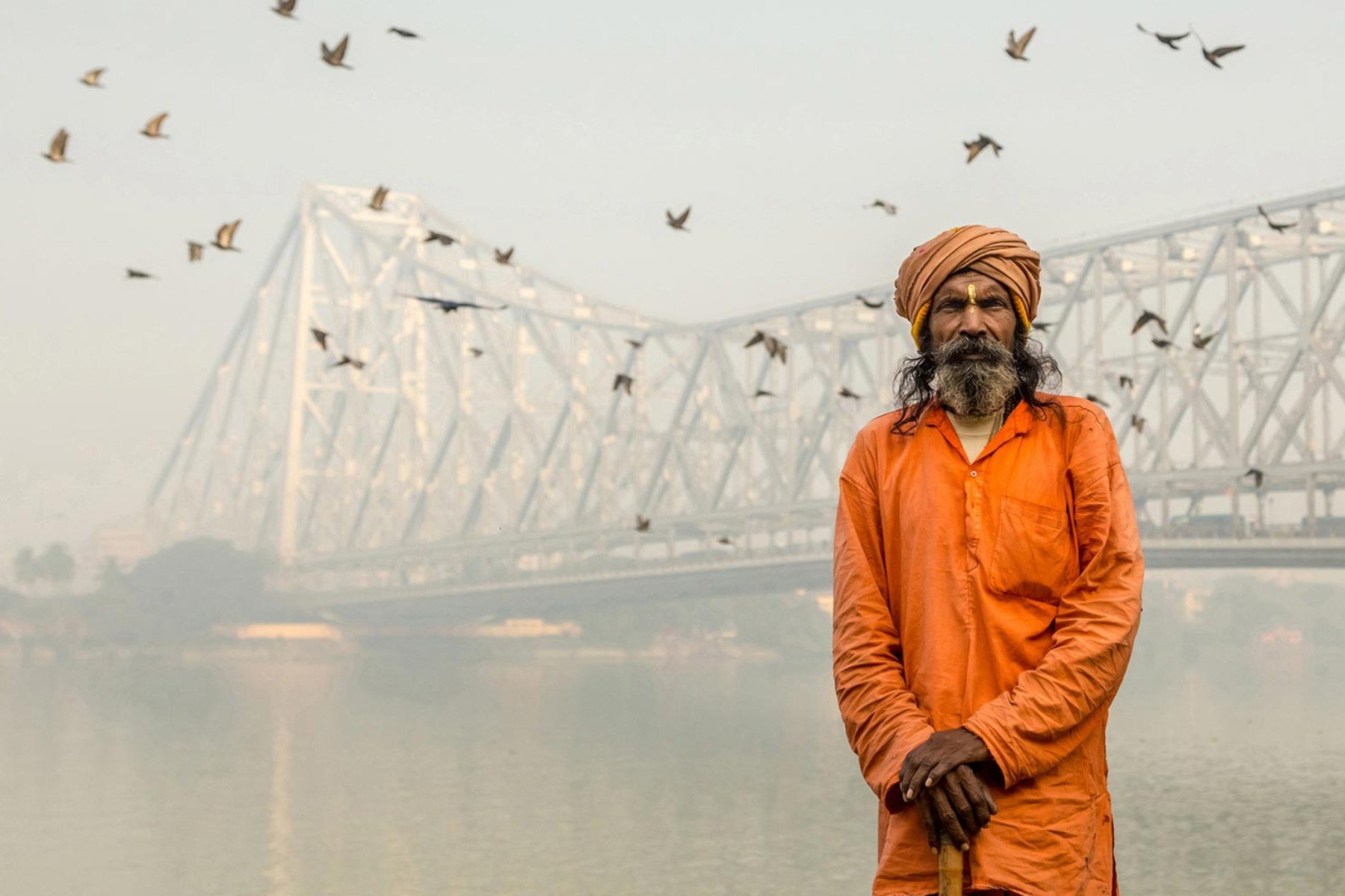 People Portrait photograph man with orange clothes standing before bridge