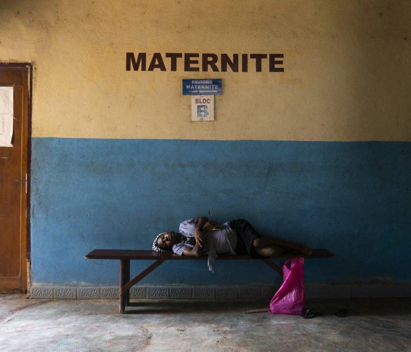 """Título: """"Madonna del parto"""" - Camerún Este retrato es parte de un proyecto a largo plazo sobre las consecuencias de la guerra. En este caso, la guerra civil en Camerún que comenzó hace dos años. Candice descansa en el banco después de recorrer más de mil kilómetros para dar a luz en el hospital de Édea. El pueblo está ubicado cerca de Bamenda, en la parte de habla inglesa del país. Debido a la guerra entre los separatistas 'Amba boy' y el ejército, la zona está sitiada, las carreteras casi todas bloqueadas, hay numerosos puestos de control y escasean los alimentos y las drogas. Por ello, decidió viajar durante casi dos días para llegar a un hospital seguro."""