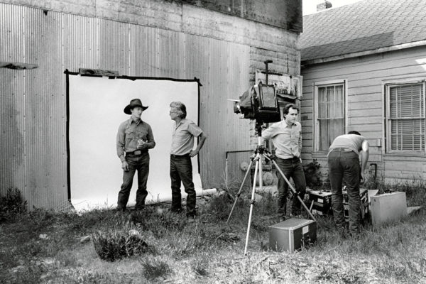 Richard Avedon, second from left, talking with a cowboy in Augusta, Montana, with Ruedi Hofmann, third from left, assisting on the shoot in 1983 © Laura Wilson