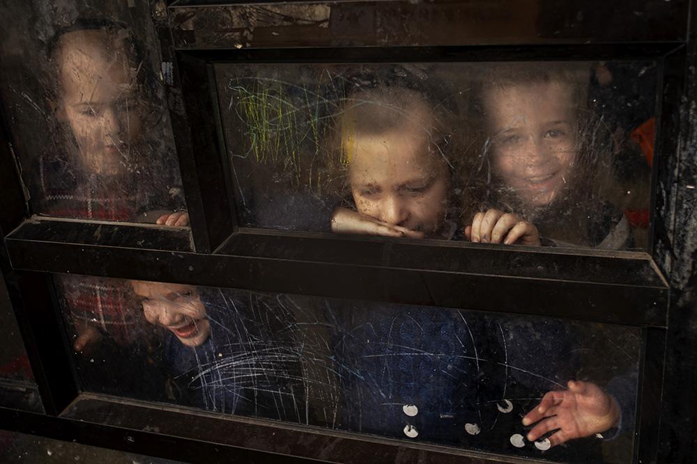Children looking through the glass, in Bnei Brak, Israel, 2000