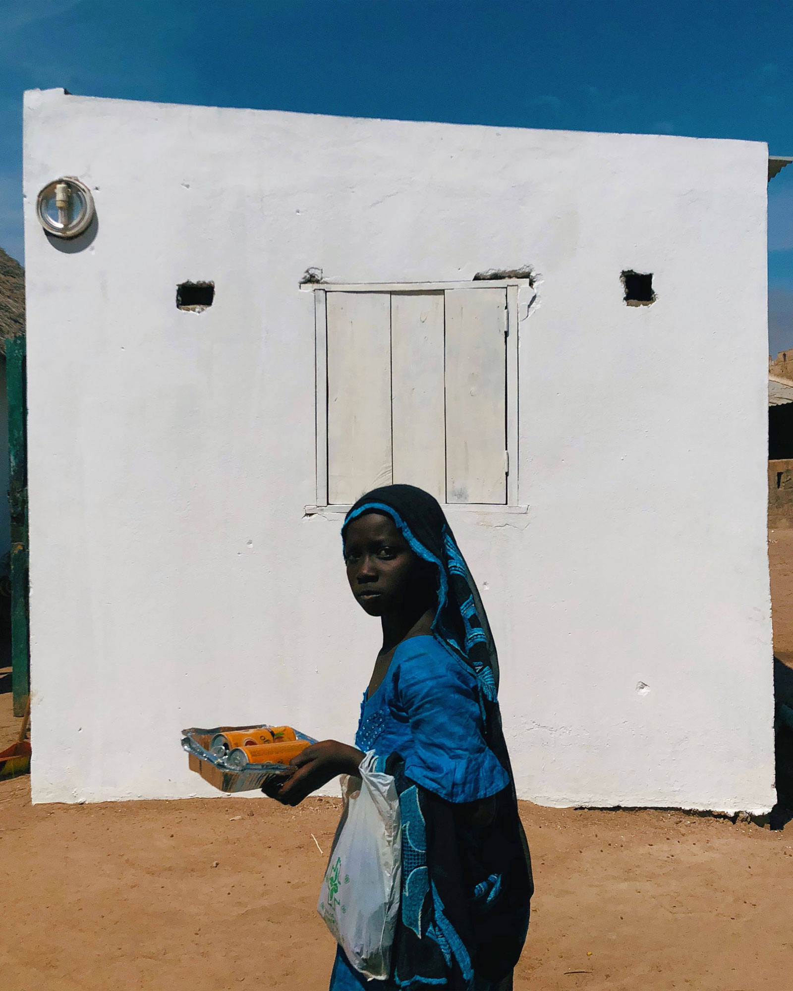 A young girl walks past a house in a remote village in Senegal